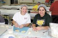 Kathleen Boehme, left, and Katrine Aboujaoude make meat pies ahead of the Lebanese Food and Cultural Festival on April 12-13.