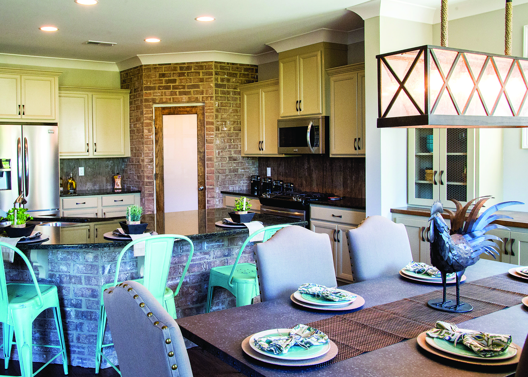 Real brick was used as a heavy accent in the kitchen of the Miner model home   The pantry was built with a brick inlay and the island is also bricked. Industrial Chic  Liberty Park Model Home Draws on Area s Mining