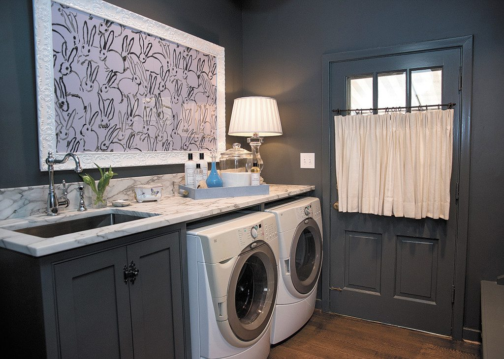 Artwork by Hunt Slonem stands out against the laundry room's charcoal gray walls.