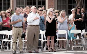Members of the community stand for the Pledge of Allegiance.
