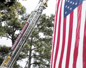 Stars and Stripes hang from Mountain Brook fire truck ladder during the ceremony.