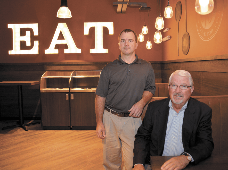 new home: Ready to welcome shoppers to the new Western Market in Mountain Brook's Lane Parke are Ken Hubbard, Western Supermarkets' owner and CEO, right, and his son, Brett Hubbard, deli, bakery and floral specialist. They're in the store's upstairs dining area, where people are welcome to eat, drink and use the free Wi-Fi. The store's grand opening is set for Oct. 13. Journal photo by Jordan Wald.