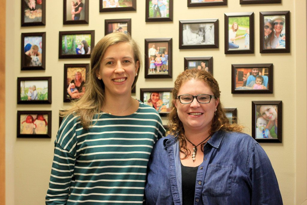 """Program Coordinator Katherine Wood and Executive Director Mary Michael Kelley in front of their """"donor wall"""" which has pictures of mothers they've worked with. Journal photo by Kaitlin Candelaria"""