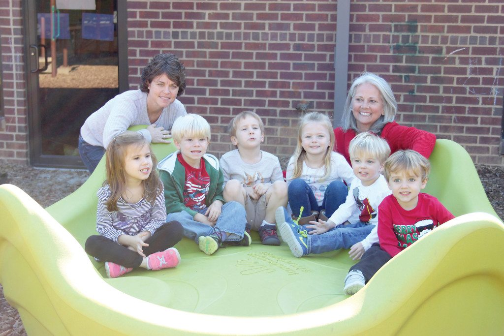Mitchell's Place occupational therapist Becca Wood and Executive Director Sandy Naramore pose with students on the new Spinner, one of several new items purchased for the playground. Journal photo by Kaitlin Candelaria