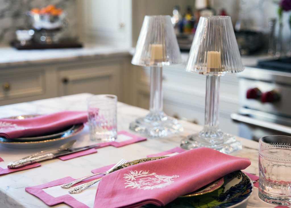 Pink linens with monograms brighten the kitchen with an unexpected color.