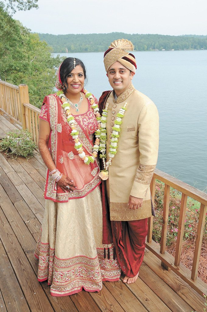 Avani and Milind Patel pose for a portrait in front of Lake Mitchell after becoming man and wife in a formal Indian wedding ceremony.