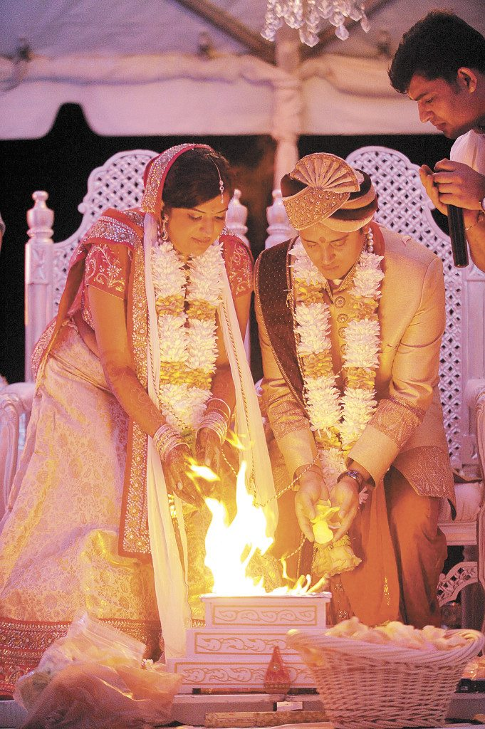 The couple pours sugar, rice and herbs into the ceremonial fire. The fire symbolizes a divine presence.
