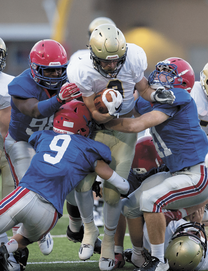 A host of Vestavia defenders stop Briarwood's J.R. Tran Reno in the Rebel's 20-7 win over the Lions last week. Photos by Marvin Gentry.