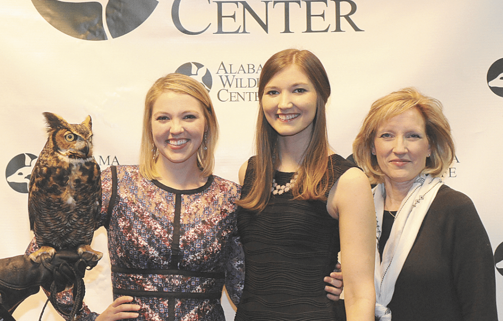 From left, Kaley Johnson, Kendall Johnson, and Lisa Langer meet AWC's Great Horned Owl at last year's Wild About Chocolate gala. Photo special to the Journal.